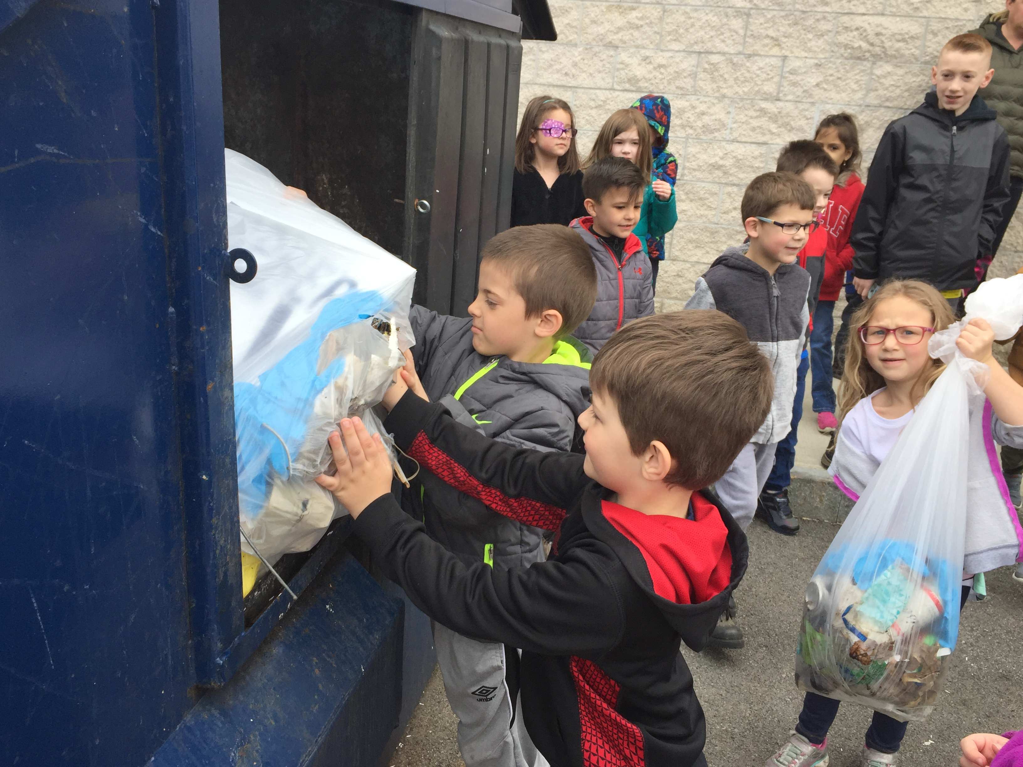 children put trash into a trash dumpster