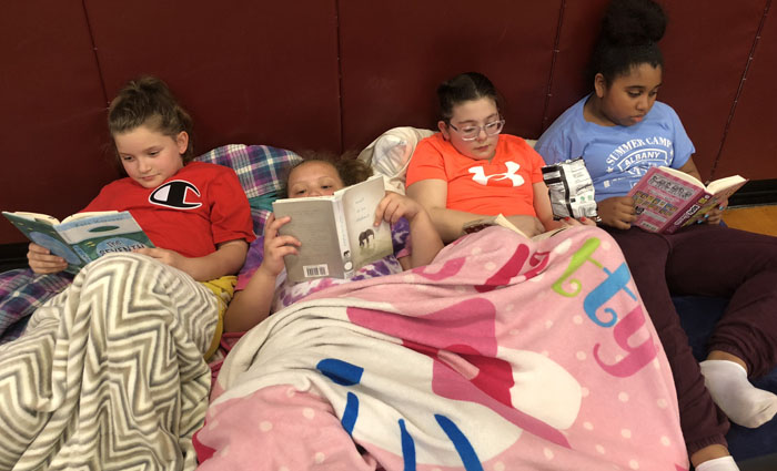 4 kids reading on bean bags covered with blankets