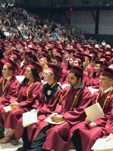 graduates seated in their caps and gowns