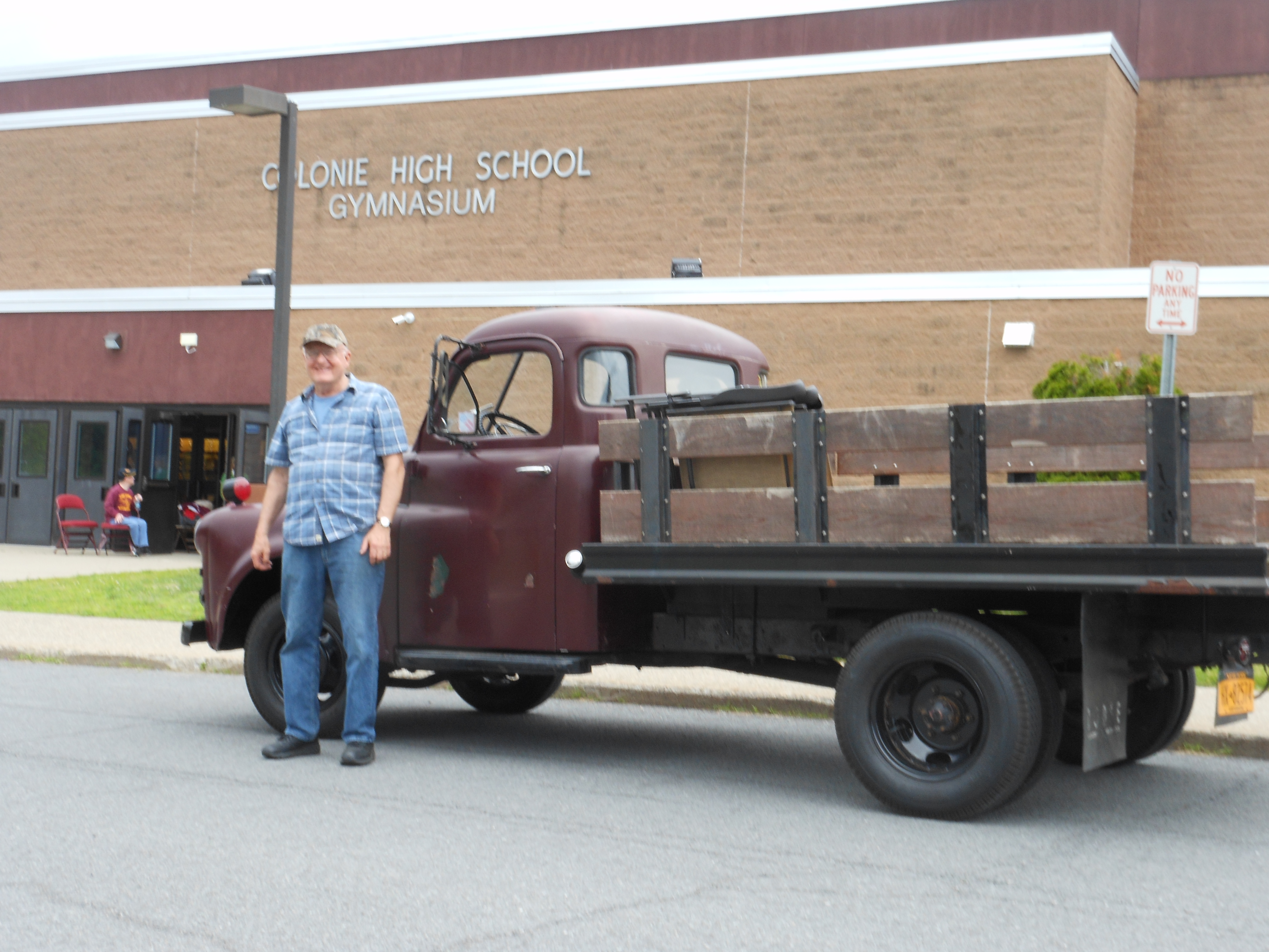 man stands in front of his antique truck