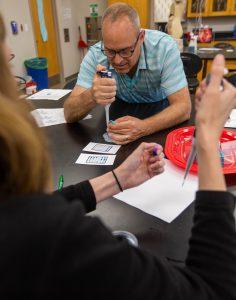 teacher uses an eye dropper to dispense liquid