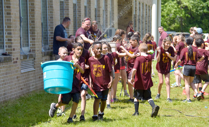 boy carries a large bucket of water surrounded by hosed down classmates at field day