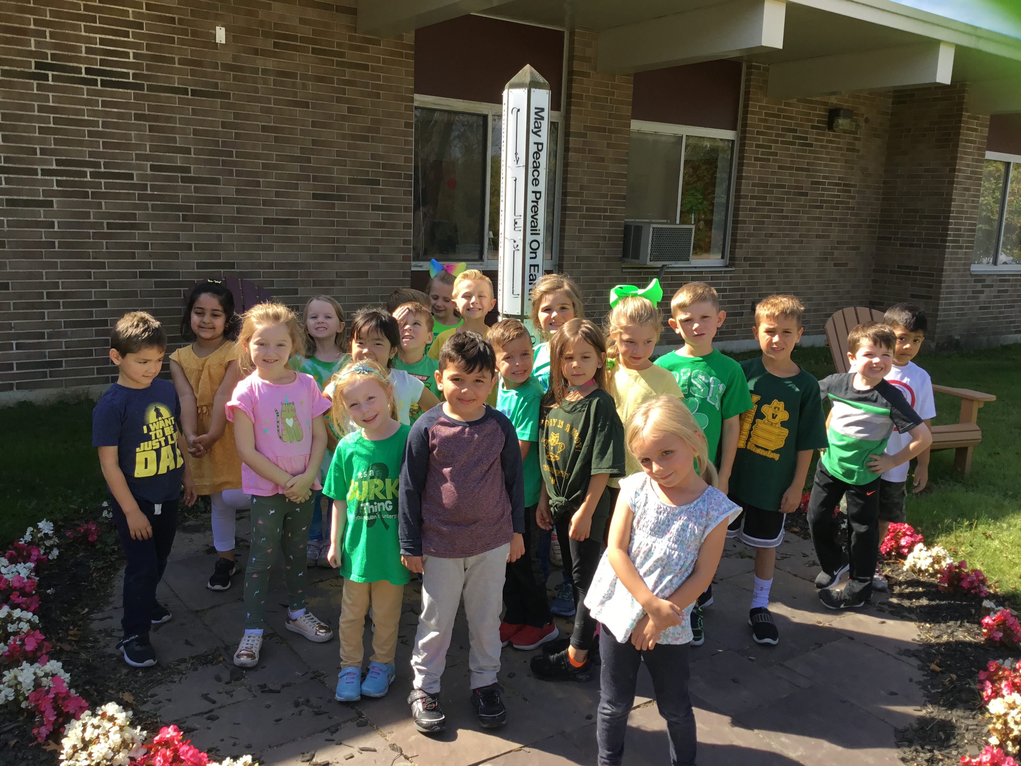 group of kindergartners stand in front of the school peach pole