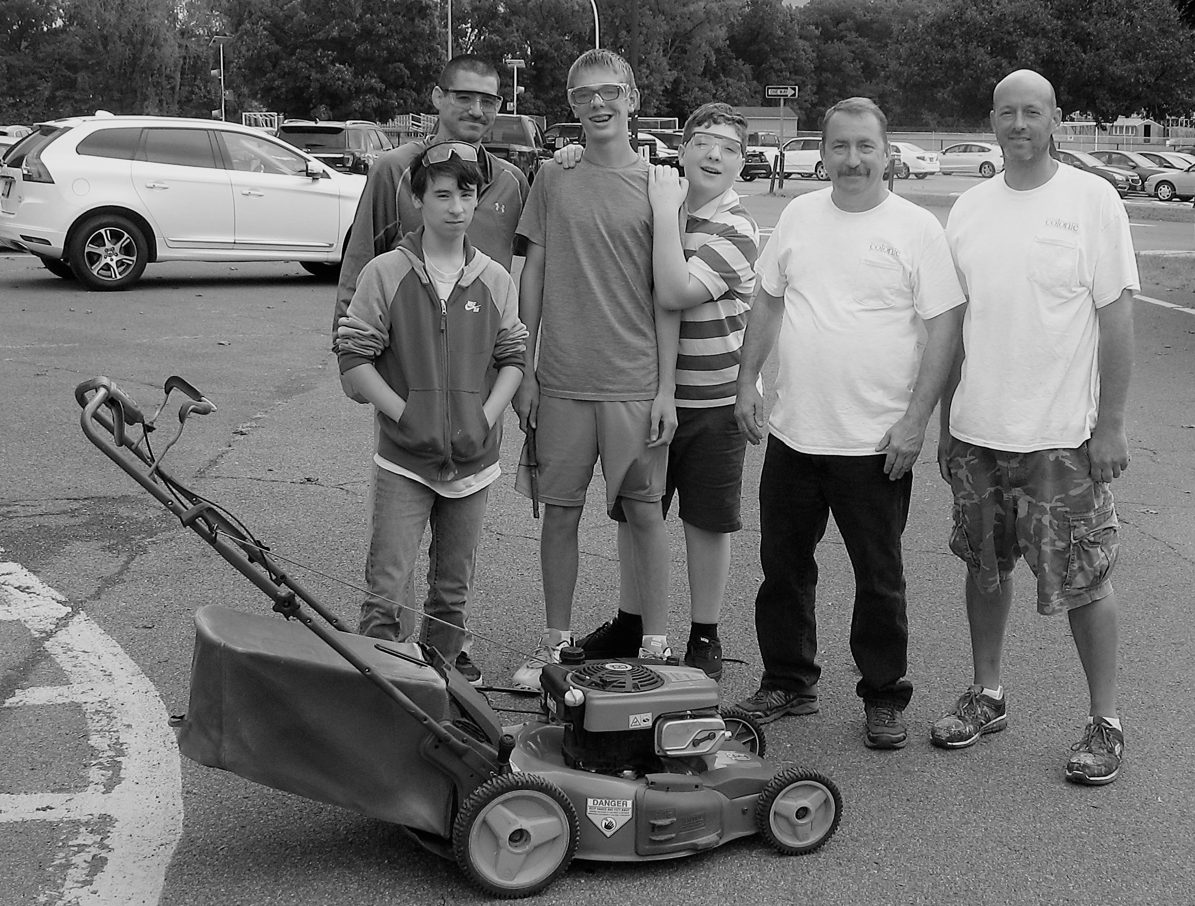 students and staff stand with a lawn mower