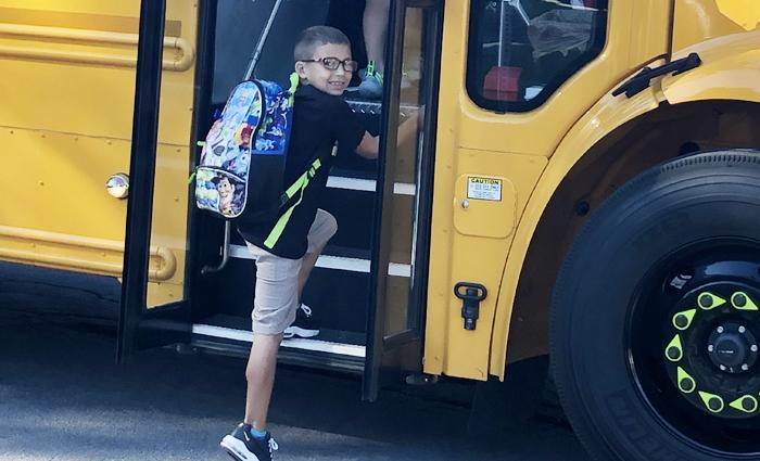 boy gets on school bus