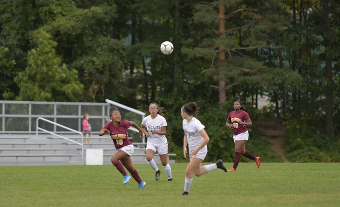 girl soccer players run after ball