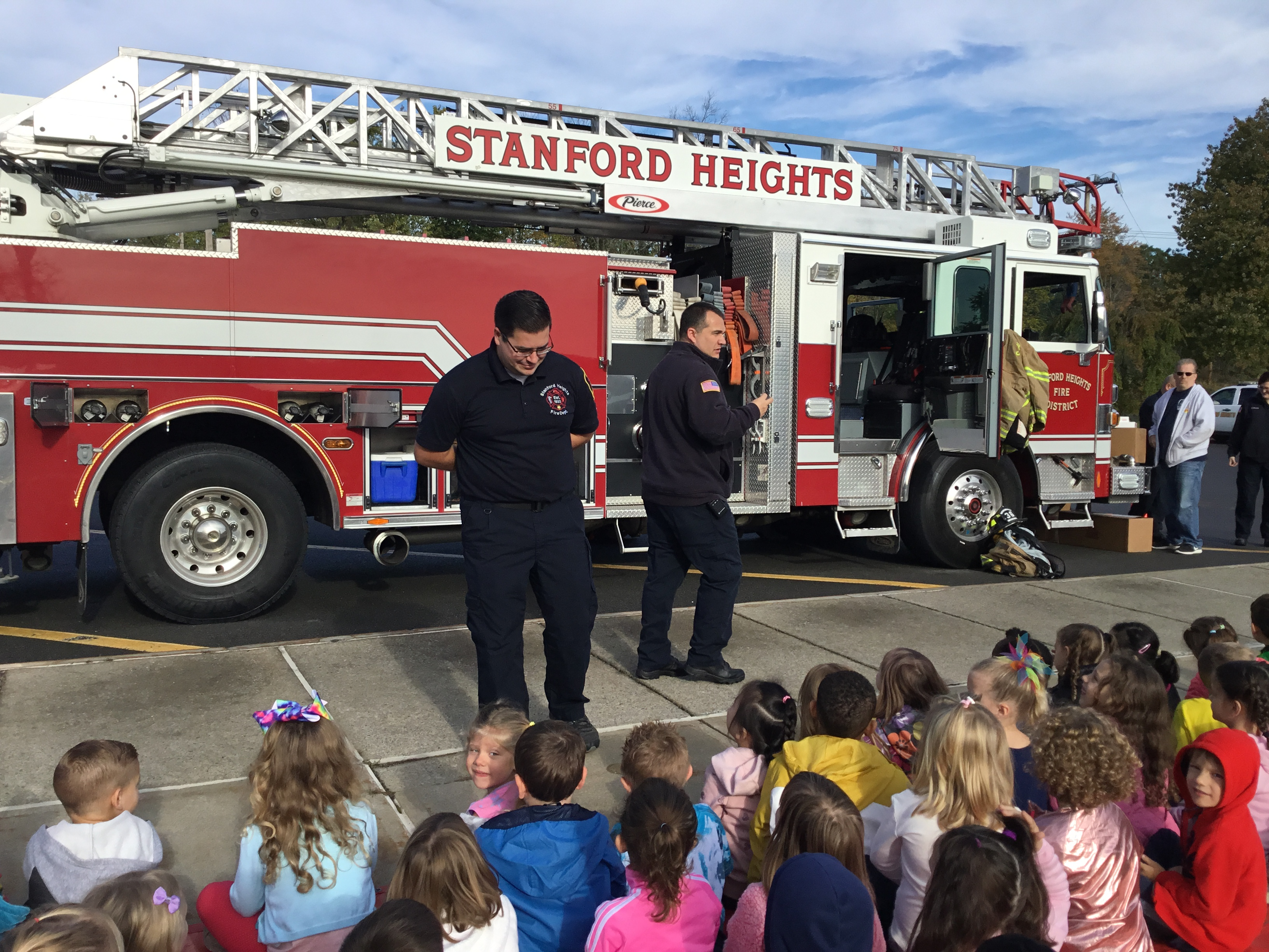 firefighters talk to students in front of big fire truck