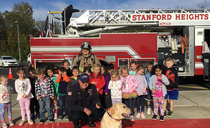 children stand in front of big firetruck