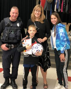 boy with soccer ball, police officer and other adults