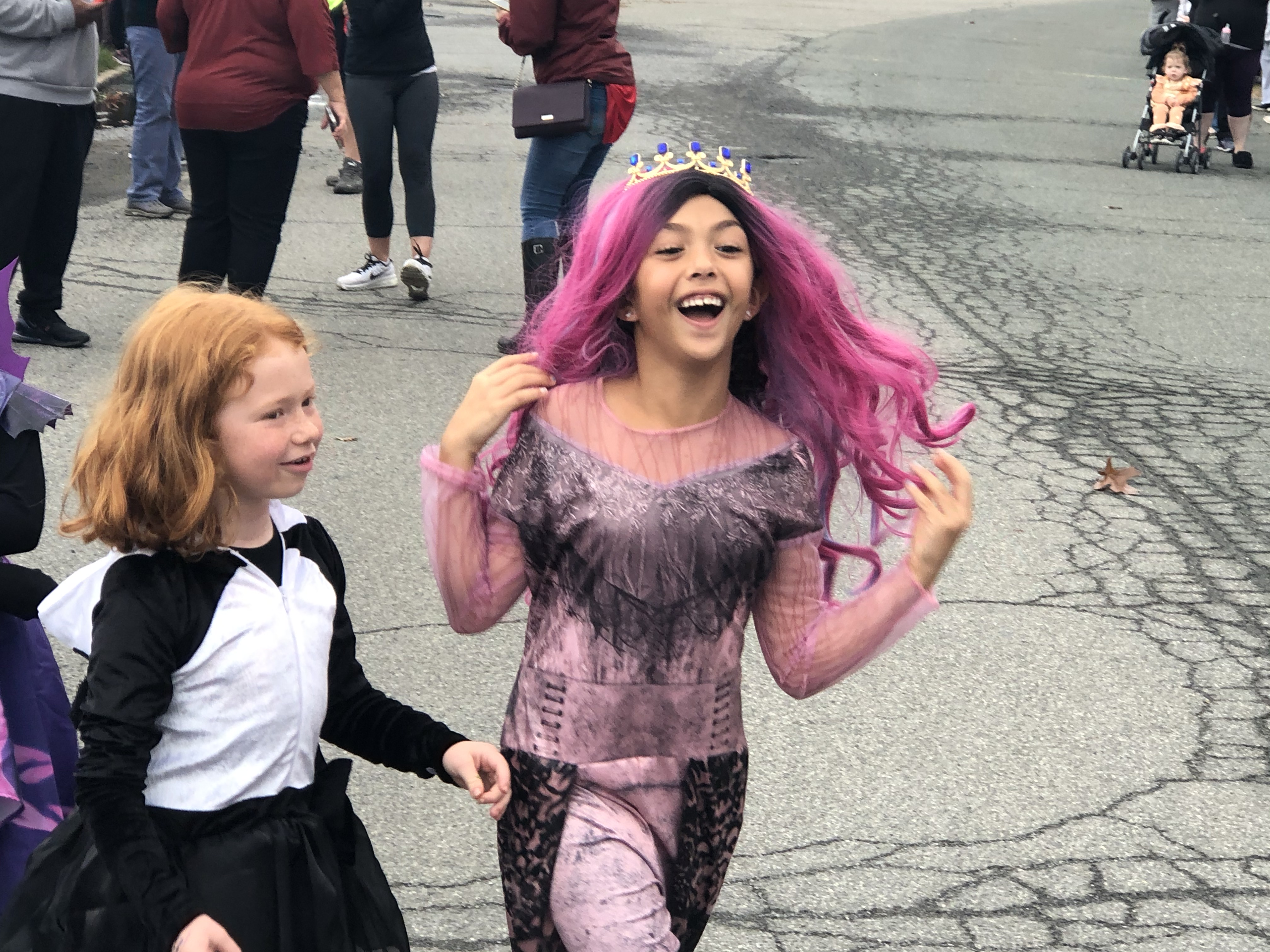 two girls march in Halloween costumes