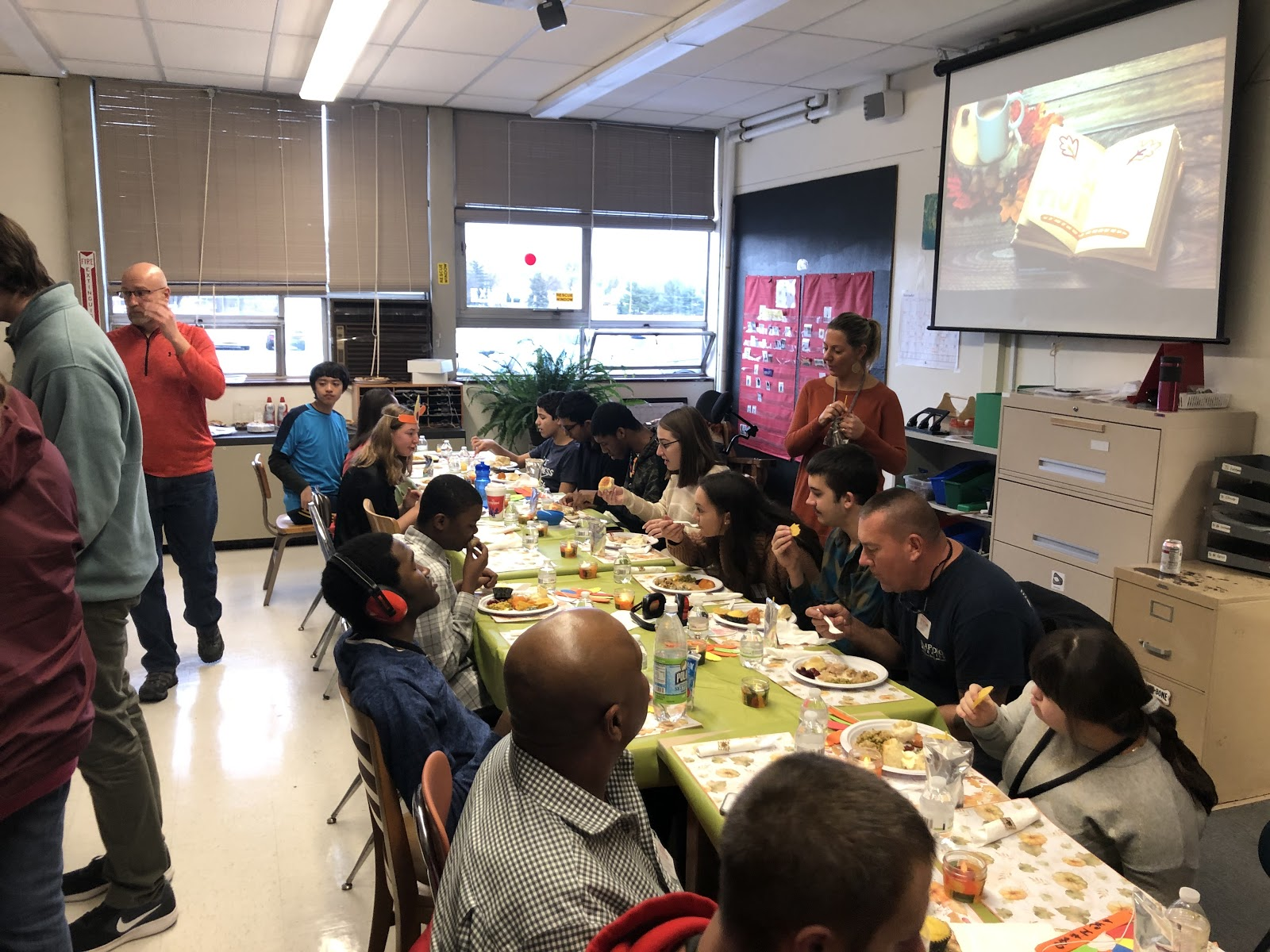 staff and students enjoy Thanksgiving dinner together at large table