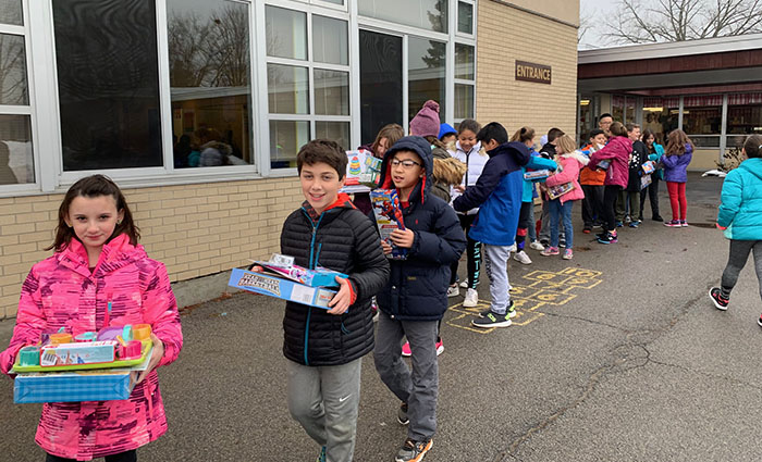 children carry gifts to the bus