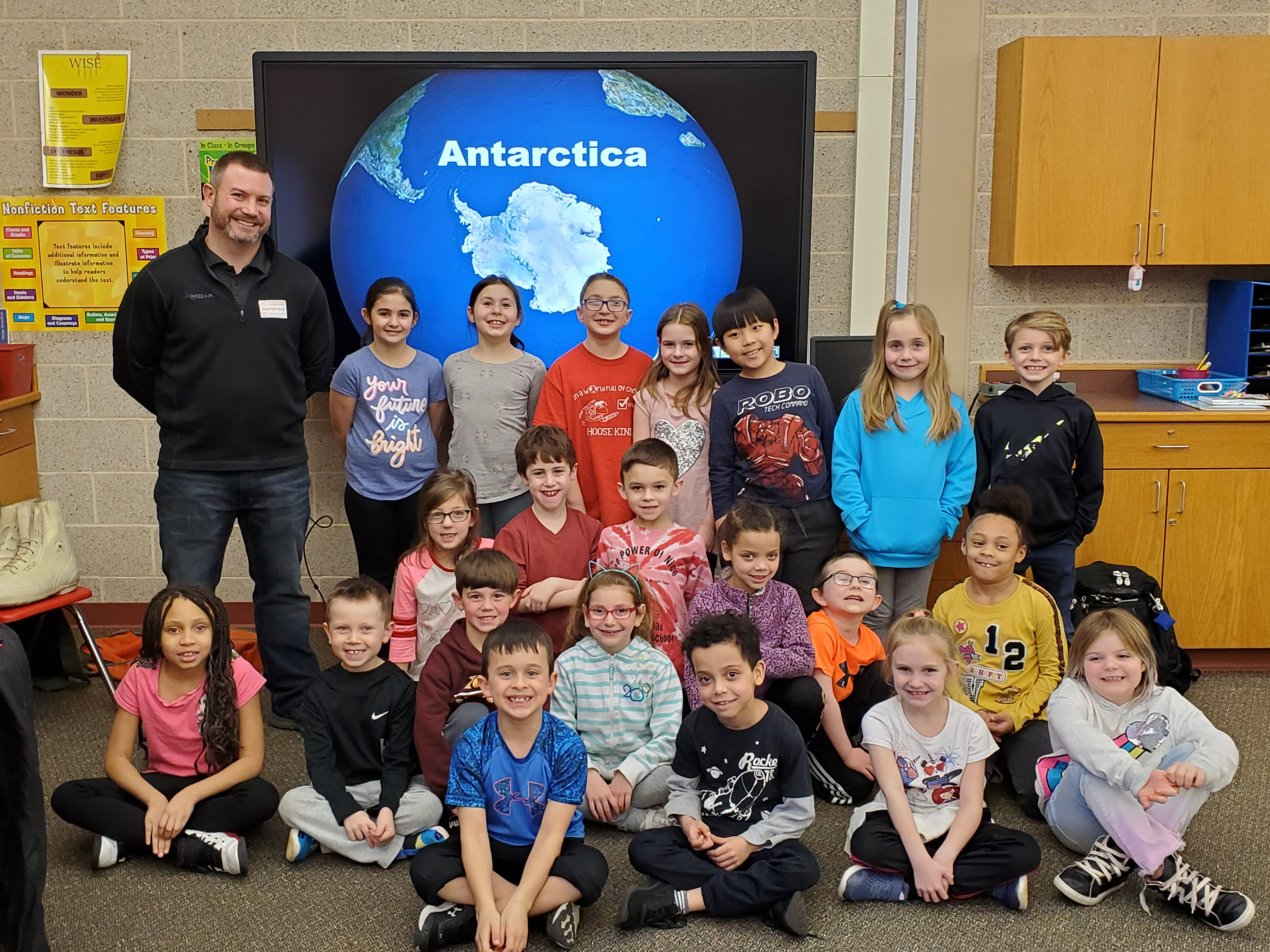 Students post for a photo infront of a photo of Antartica