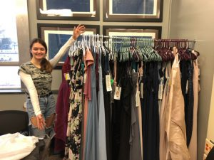 student poses with a rack full of dresses