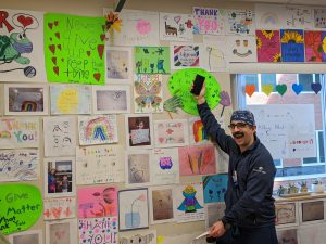person stands in front of a wall full of student artwork