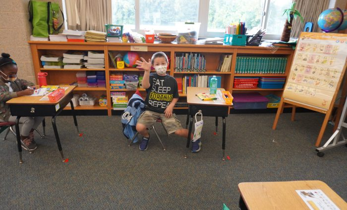 student waving as he is sitting at his desk at school